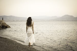 Girl standing on the beach with white dress