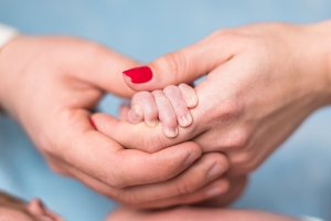 Parent hands holding baby's hand