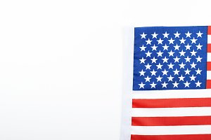 Studio shot of small bright USA flag lying on white background. Isolated. Copy space.