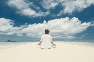 Young man meditating in Lotus position on a sandy beach