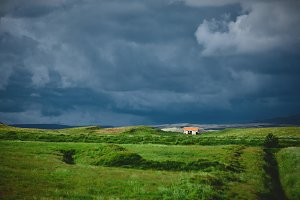house in the field on dark cloudy sky background
