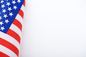 Studio shot of small bright flag of USA lying on white background. Copy space.