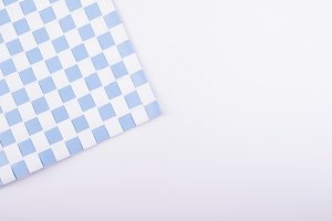 Background of tablecloth with white and blue squares on white background. Isolated.