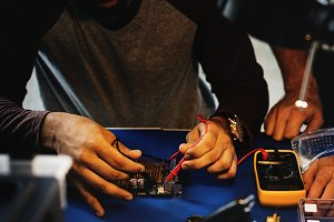 Man measuring computer circuit board