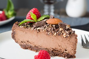 Chocolate cheesecake decorated with raspberries and mint