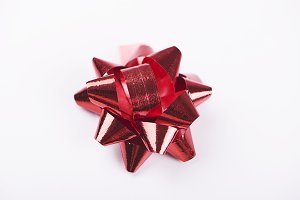 Bow with star shape of red color decoration paper on white background