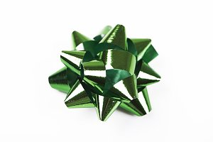 Bow with star shape of green color decoration paper on white background
