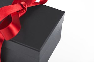 Black box with red ribbon on white background. Copy space.
