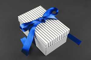 White box with black drawstring tied with blue bow on black background. Copy space.