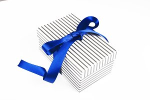 White box with black drawstring tied with blue bow on white background. Copy space.