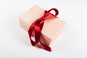 Pink box tied with red bow on white background. Copy space.