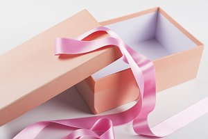 Pink box next to pink ribbon on white background. Isolated.