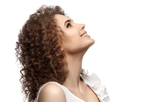 Beautiful curly girl looking up and smiling, isolated on white background.