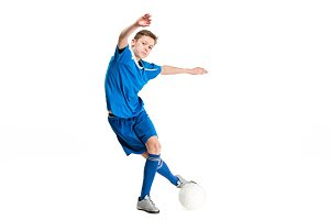 Young boy with soccer ball doing flying kick