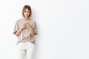 Young Caucasian female with short hairstyle, dressed casually, keeping cell phone in hands, typing messages, listening to music with earphones, isolated over white background. Youth and technology