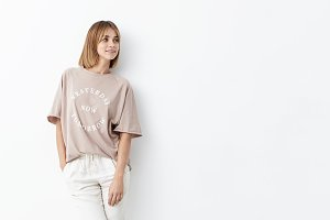 Beautiful young female with boobed hair, wearing loose shirt and white trousers, modeling against white background, looking aside while waiting for her boyfriend, going to have walk in with him