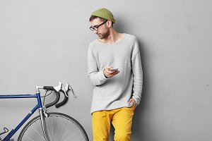 Serious unshaven young man in trendy wear posing at concrete wall and looking at his fixed gear bike, studying its characteristics while posting ad via classified website, putting it up for sale
