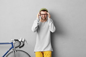 Sickness, migraine, unwellness and health problems. Picture of stylish unshaven Caucasian guy wearing yellow trousers, oversize sweatshirt, green hat and glasses squeezing temples because of headache