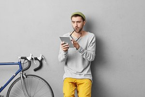 Indoor portrait of handsome male student reading attentively lecture on modern tablet, taking off glasses, being involved in studying, isolated over grey background, standing near his bicycle