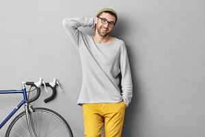 People, travel, leisure and lifestyle concept. Smiling young hipster man in fashionable clothes standing near bike while waiting for his companion to ride together and to explore big city or town
