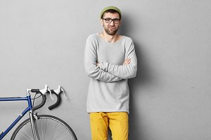 Unhappy bearded man wearing loose sweater and yellow trousers, keeping his hands crossed while going to ride bicycle. Young hipster student waiting for instructor to learn bicycle handling skills