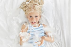 Happy childhood concept. Leisure, fun and relaxation. Top picture of adorable blonde freckled little girl preschooler looking at camera through flying feathers after pillow fighting in her room