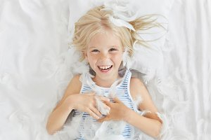 Funny small child with light hair, lying on white bedclothes, feeling joy while catching feathers, having fun with her friends. Cute blue eyed girl wanting to sleep, playing in bed. Childhood concept