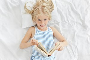 Indoor shot of cheerful adorable little girl with blonde hair lying on white pillow in her bedroom, enjoying reading fairytale. Blue-eyed cute female child reading instead of napping, having sly look