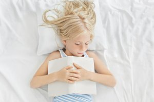 Top shot of adorable little female child napping in bed. Cute baby girl with freckles and blonde hair having quiet sleep with open book after reading interesting story, seeing nice sweet dreams