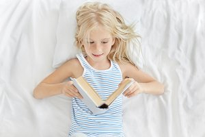 Sweet little blonde 7-year old girl of European appearance resting in white bed, looking in open book with interest while reading fairytale before sleep. People, leisure and childhood concept