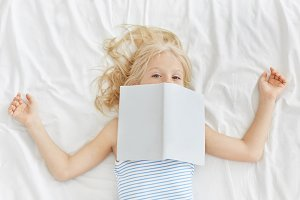 Lovely girl wearing pyjamas, reading fairy tales in bed, covering her face with book, going to have sleep. Freckled small female kid waiting for her mother to read her different magnificent stories