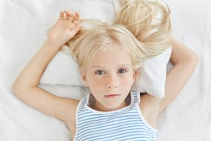 Adorable little girl with freckled skin having sick look, while lying on white bed of hospital, looking with her blue charming eyes, wanting to have rest. Sick girl on white bedclothes lying in bed.