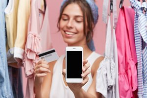 Female with happy expression standing near rack with clothes over pink background, keeping in hands credit card and modern mobile phone, being glad to buy garment online. People, online shopping