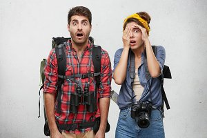 Shocked hitch hikers carrying backpacks, binoculars and camera, being tired after waiting for long time car. Female hiding her face while being afraid of someone. Two people with surprised expression