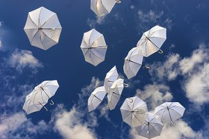 White umbrellas in the blue sky