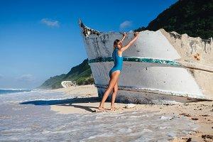 Woman in swimwear walking on sandy beach during daytime near broken ship
