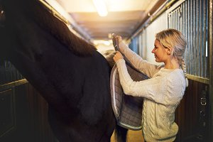 Woman standing in stables prepping her horse for a ride