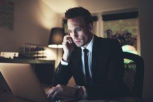 Man browsing laptop and talking the phone