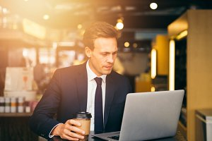 Focused businessman drinking coffee in a cafe working online