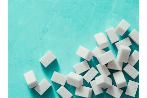 Top view of white sugar cubes on blue concrete background