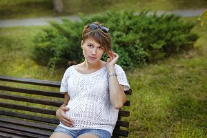 Pregnant girl sitting on bench