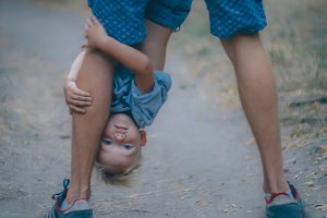 Kid boy hugging his father's leg