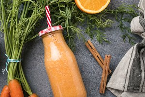 Healthy carrot smoothie with orange and cinnamon in glass bottle
