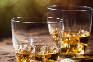 Whiskey with ice in glasses on rustic wood background