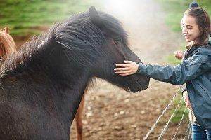 a woman stroking a horse