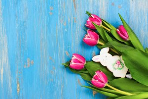 Pink tulips and bunny cookie on blue background