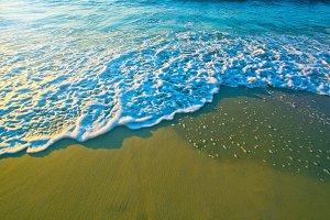 Blue sea waves on sand.
