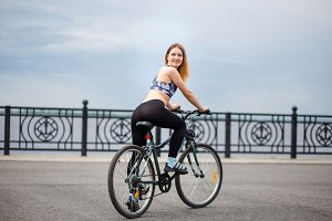 Outdoor Portrait Attractive Athletic girl with bike