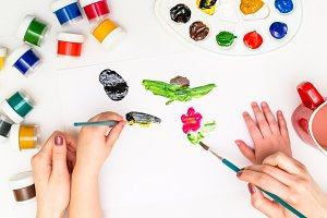 Child's hands painting a flower