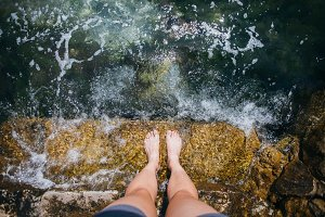 Female feet in clear blue water